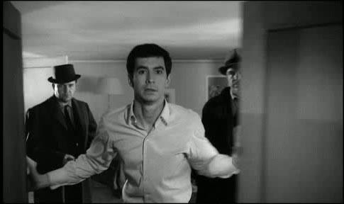 Joseph K. öffnet die Tür zum Zimmer des Frl. Bürstner, beobachtet von den Beamten.