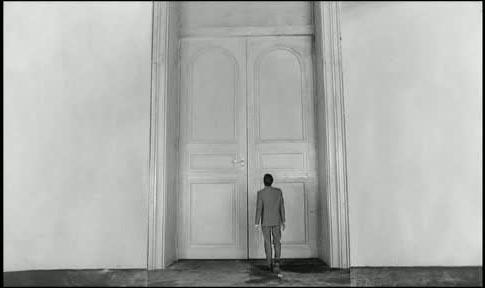 Joseph K. steht draußen vor der Tür des Gerichtssaals
