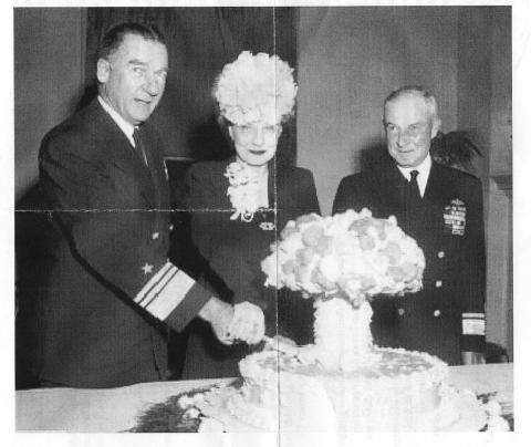 Zwei amerikanische Militärangehörige und eine Frau in Festtagskleidung schneiden eine Torte in Form eines Atompilzes an.
